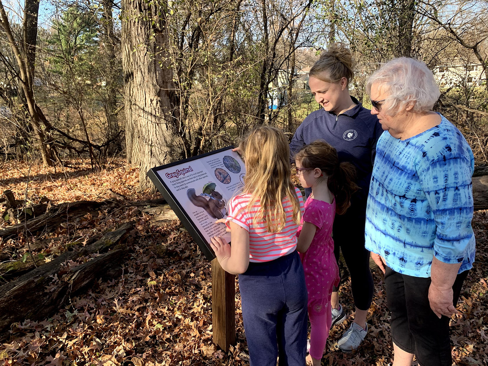 A family surrounding a sign in the woods including two young girls, a mother, and a grandmother.